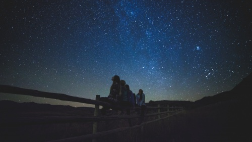 People sitting on a fence looking up at the night sky full of stars.