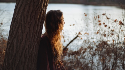 A young woman leaning against a tree looking out over a lake.
