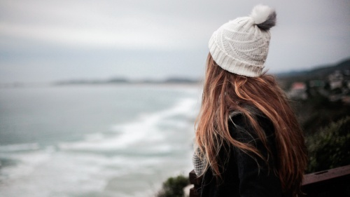 A young woman looking out over the ocean.