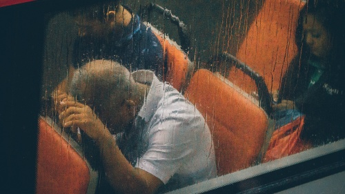 People riding a commuter train while raining.