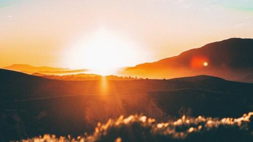 A sun setting over hills.