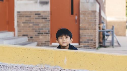A little boy hiding behind a yellow wall.