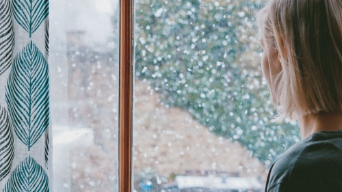 A young woman looking out a window as snow falls.