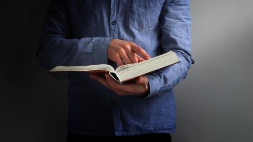 A man wearing a blue shirt holding a Bible.