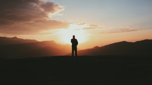A silhouette of a person stand on a hill with the sun in the background.