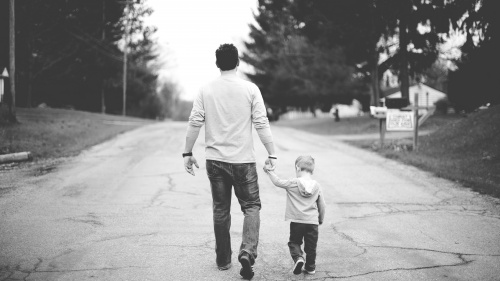 A dad walking with his young child.