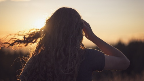 A young woman looking at the setting sun.