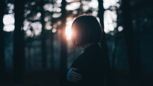 A young woman standing in a patch of trees with the sun shining through.