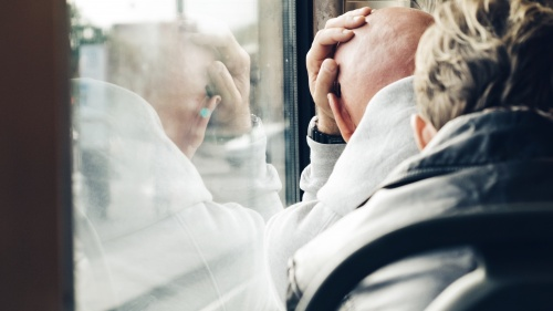A man leaning his head against a train window.