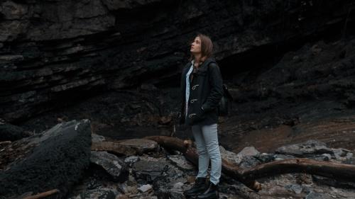 A woman hiking on a rocky path.