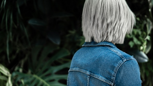 The back of young woman wearing a blue jean jacket.