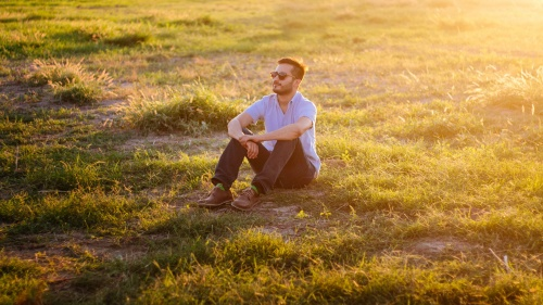 A man sitting in a field with the sun rays shinning.