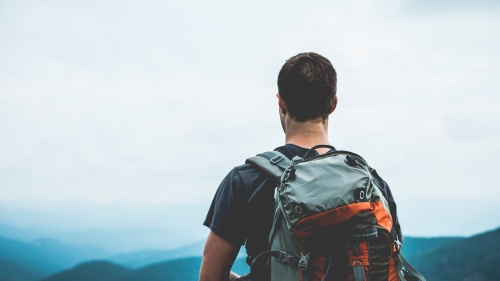 A guy wearing a backpack at the top of a hill.