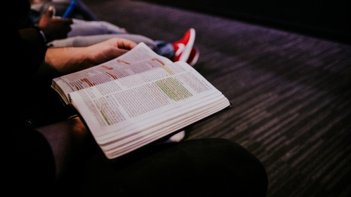 A young person reading a Bible.