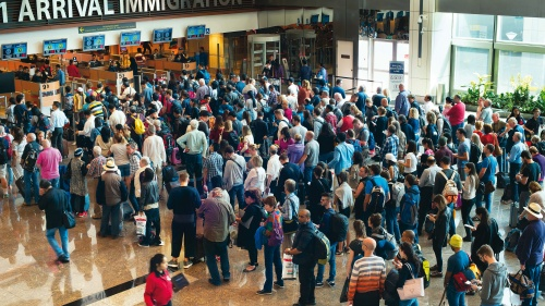 Airport travelers standing in line to go through immigration customs.