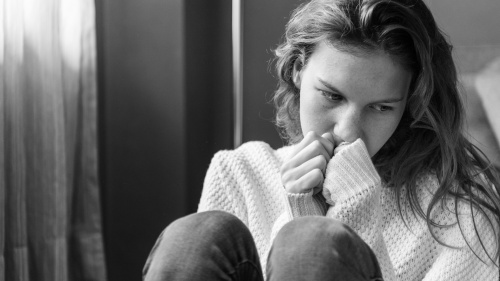 A sad woman sitting on the floor.