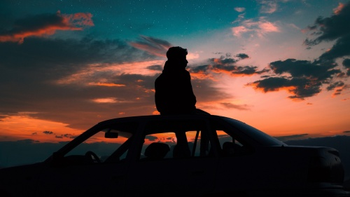 A young man sitting on the top of a car watching the sunset.