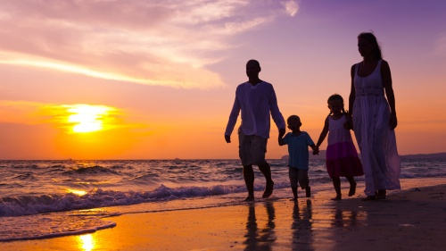 A family of four walking on the beach at sunset.