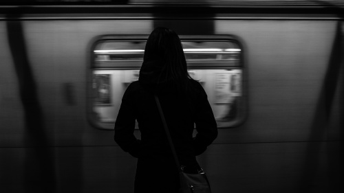 A woman standing by a subway train as it passes by.