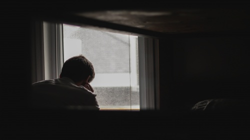 A silhouette of a man sitting by a window.