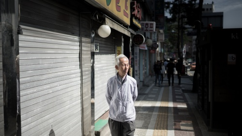 An older man walking down an alley street.