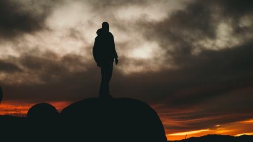A man standing on a boulder.