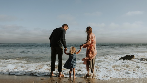 A family wading in the waves of the ocean.