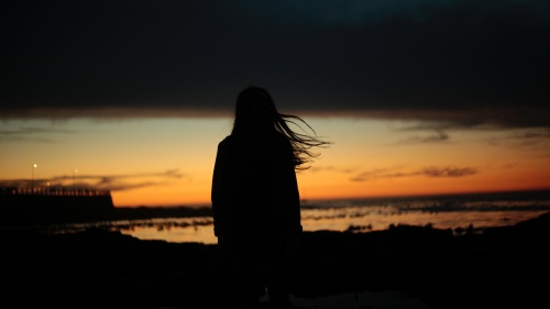 A silhouette of woman at sunset.