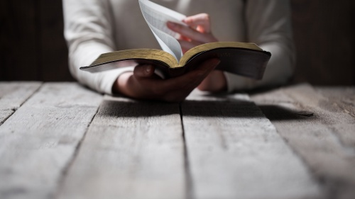 A person reading a Bible at a table.