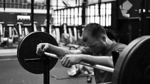 A man resting his arms on a weight lifting bar.