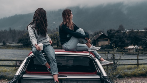 Two young adult women sitting on top of a car.