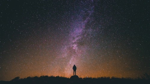 A person standing at night with stars in the background.