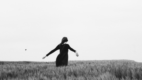 A woman with her arms open walking through a field.