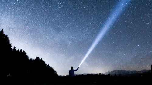 A person pointing a flashlight beam up into the night sky.