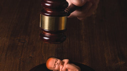 An illustration of newborn baby laying below a judge's gavel.