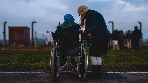A woman helping an elderly person in a wheelchair.