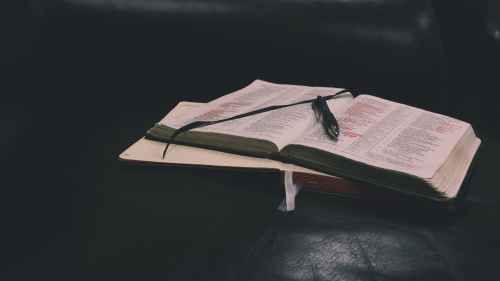 A Bible and notebook laying on a table.