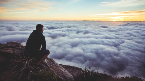 Photo of man thoughtfully squatting at the top of a cliff looking at the clouds.