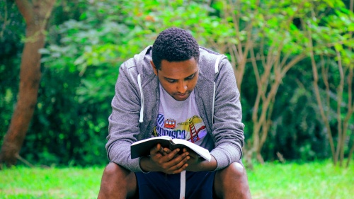 A man sitting on a bench reading a Bible.