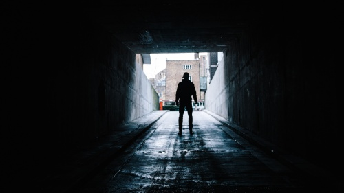A man walking out of a dark tunnel.