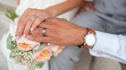 Photo of bride and groom holding hands.