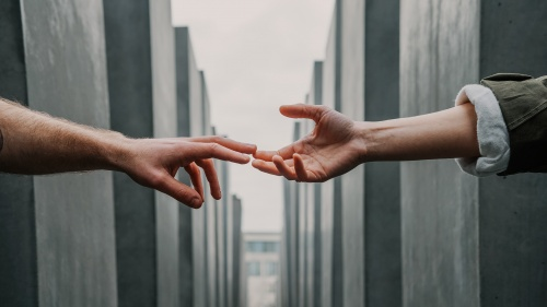 One person reaching out to touch the hand of another person.