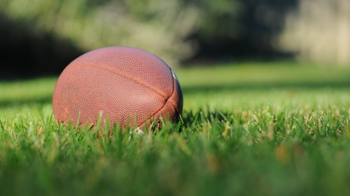 An American football on a grass field.