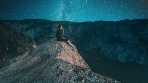 A young man sitting on a rock looking at the night sky.