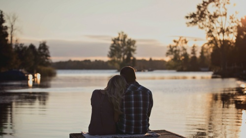 A couple sitting beside each other on a boat dock.
