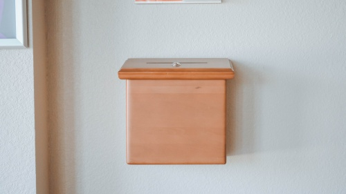 A box attached to the wall where one could drop in money at a church.