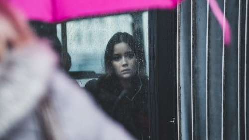 A woman looking out a window when it is raining.