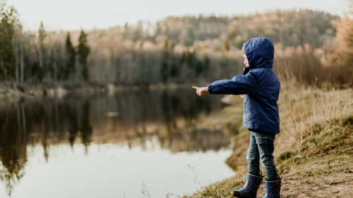 A little child standing by a lake pointing.