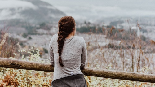 Girl leaning against a fence looking at a valley.