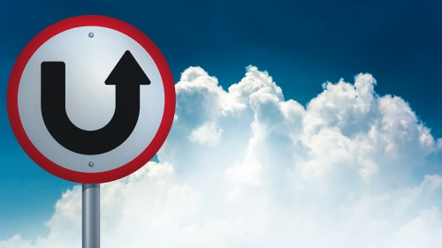 A u-turn type sign with the sky and clouds in the background.